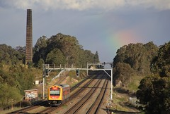 2701 drops downgrade into Metford as a rainbow shines down between rain showers (bukk05) Tags: 2701 railpage:class=344 railpage:loco=2701 rpaunswhunter rpaunswhunter2701 world explore export engine earth railway railroad railpage rp3 rail railwaystation railwaystations railcorp railmotor railcar train tracks tamron tamron16300 trains tourist travel rainbow photograph photo passenger passengertrain loco locomotive horsepower hp holiday flickr diesel dmu dieselmultipleunit station standardgauge sg spring 2016 australia artc zoom canon60d canon clouds huntervalley hunter nsw newsouthwales nswr newcastle mainline metford maitland rain chimney smokestack signal trees tree