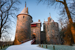 Castell Coch at Dawn (welshio) Tags: uk winter moon snow cold history castles southwales wales fairytale dark landscape dawn golden early europe shadows sinister stonework gothic towers 19thcentury cardiff victorian atmosphere eerie holes mysterious drawbridge arrow welsh monuments picturesque lightandshadow portcullis folly faerie forts pictorial buttress rampart gothicrevival romanticism castellcoch castlecoch redcastle welshcastles marquessofbute williamburges romanticlandscape britishlandscapes welshlandscapes arrowholes gettyholidays2010 welshlandmarks
