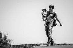 Out for a walk (.Chris Lee) Tags: summer people blackandwhite bw baby white black monochrome hat sunglasses garden walking children botanical outside outdoors person glasses virginia kid movement nikon child arm path father hill young monochromatic swing telephoto parent pace grayscale care 70300mm meadowlarkbotanicalgardens tamron stroll botanicalgardens slope carrying greyscale dx meadowlark nikondx tamron70300mm d7000 nikond7000
