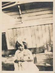 Sad little girl holds her doll (simpleinsomnia) Tags: old white black girl monochrome wall vintage found weird blackwhite blurry doll sad little antique creepy odd photograph scarey littlegirl scared foundphotograph