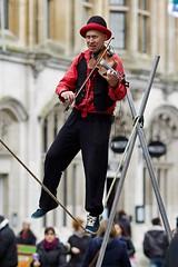 Fiddler on a rope, Canterbury (chrisjohnbeckett) Tags: street red music rope canterbury violin instrument fiddle entertainer balance performer violinist fiddler slackline canonef135mmf2lusm chrisbeckett