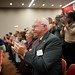 Tom Cunningham and other audience members clap at the announcement of the generosity of the Park Foundation.