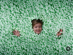 Fragile (Xlavius) Tags: people green girl goofy fun soft pretty child julia little daughter posing chips foam packaging safe portfolio courier package fragile careful shipment breakable