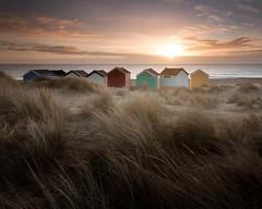 Spectators [Explored] (jellyfire) Tags: england sky beach water grass sunrise canon landscape dawn suffolk sand day cloudy unitedkingdom dunes southwold beachhuts goldenhour eastanglia canonef1740mmf4l 1740mmf4lusm canon5dmkii