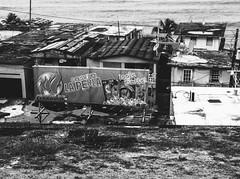 Know The Ledge (JMJ Cinematics) Tags: puertorico blackandwhite landscape pr borinquen streetphotography monochrome monochromatic slums slum caribbean island isla caribe jmjcinematics josemiranda photojournalist photojournalism iphone iphone3 sea ocean water homes ghetto hood life struggle architecture beach beaches oldsanjuan sanjuan laperla travel mobile mobilephotography iphonephotography