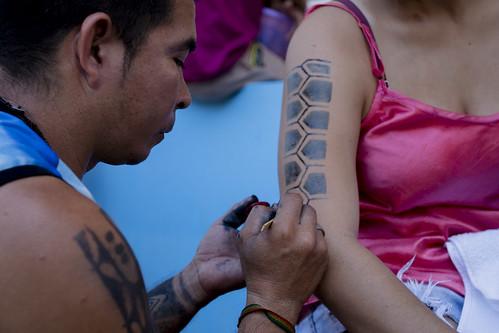 Indígenas pintando participantes do evento