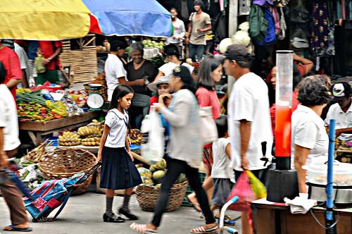 Schoolgirl walks through a busy street market alone