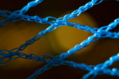 Sunlit Goal (brucetopher) Tags: sunlight light bokeh twine vinyl monofilament monofil mesh strand string braid net goal orange yellow blue loose knots diamond parallelogram shape geometric geometry tie tied