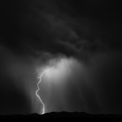In the Night (agavephoto) Tags: sky blackandwhite storm black mountains newmexico nature rain weather night clouds dark square landscape quiet nightscape desert minimal le monsoon bolt electricity lightning minimalism simple desolate  loneexposure