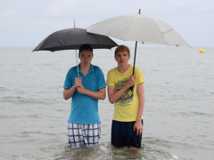 Oops ... my cell phone! (Jan van der Wolf) Tags: sea two people wet water rain yellow umbrella brothers nat geel regen paraplu twee twoguys twoboys jongens broers twobrothers 2guys map9123