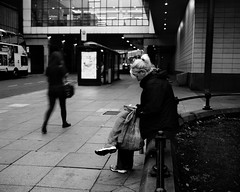 On Her Phone Waiting For The Bus - Newcastle (Richard James Palmer) Tags: mamiya7ii mamiya 7ii 80mm ilford hp5 ilfordmicrophen microphen ishootfilm shoot film iso 400 iso400 ilfordhp5 f4 newcastle northeast north east street photography streetphotography portrait black white rangefinder medium format 120 filmisnotdead analogue documentary epsonperfectionv700 epson v700 1125 newcastleupontyne upon tyne tyneandwear northern uk england urban melancholy art fineart new overcast isolated walkabout 2016 gritty gloomy abstract trapped blackandwhite monochrome