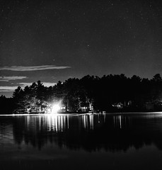 Shoreline and Stars (pano) (Eric Kilby) Tags: trees bw panorama water night stars blackwhite pond stitch pano maine shoreline acton loon