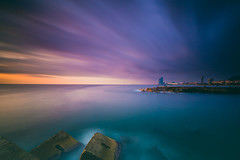 Barcelona Awakens (Maximecreative) Tags: select sky landscape sunrise morning city water travel sun light clouds europe ocean rocks horizon peaceful seascape long exposure calmness outdoors serene motion blur early wide angle lee filters skyscape piers pontoons spain