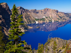 Crater Lake Blue (RobertCross1 (off and on)) Tags: 1250mmf3563mzuiko cascaderange cascades craterlake craterlakenationalpark em5 klamath omd or olympus oregon pacificnorthwest bluesky caldera crater forest lake landscape mountains reflection snow tree volcano water