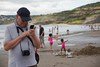 an older man with a smartphone and camera on a beach (mumography) Tags: cameraphone life camera uk family summer vacation england people holiday man beach childhood daddy fun seaside europe dad father joy grandfather smartphone cap realpeople tecnoligy