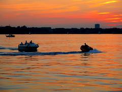im orangefarbenen Wasser der Frde rast laut einSchnellboot hin und her-hrend die anderen still den herrlichen Sonnenuntergang betrachten (evioletta) Tags: sonnenuntergang frde orange boote