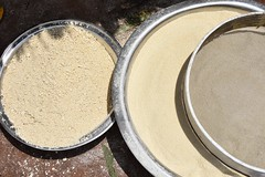 The last step in gari processing is to sieve the product for a fine texture. Unsieved gari can be seen on the left. Photo D.Dufour/CIAT-RTB