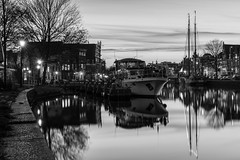 Fisherman's Bend (McQuaide Photography) Tags: haarlem noordholland northholland netherlands nederland holland dutch europe sony a7rii ilce7rm2 alpha mirrorless 55mm primelens prime sonnar sonyzeiss zeiss fe55mmf18za fullframe mcquaidephotography adobe photoshop lightroom tripod manfrotto light licht availablelight dusk twilight schemering water reflection longexposure stad city urban river spaarne rivier waterside lowlight outdoor outside waterfront architecture skyline building gebouw cityscape monochrome mono blackwhite bw blackandwhite classic authentic kortespaarne vissersbocht boat moored harbour boot calm peaceful tranquil stil