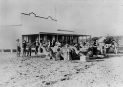 Unloading the camel team in front of the store at Boulia, ca. 1895 (State Library of Queensland, Australia) Tags: men hats goods afghan queensland statelibraryofqueensland afghani cameldriver slq