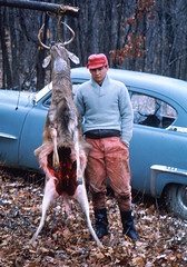 Gutted (1965) (david ross smith) Tags: trees hat leaves dead pennsylvania deer antlers redhat hunter 1960s oldcar archival middleclass 1965 bluecar gutted openfly deaddeer buttonfly rosssmith bluesweater flyopen reflectioninwindow deerhanging unbuttonedfly gutteddeer flyunbuttoned