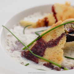 Tarte tatin of fig with espuma of cantal cheese. (annick vanderschelden) Tags: baked baking bakingpaper butter chive cooking crisp crusty dessert espuma figs foam hand humanhand incision oven pack pointofview preparation pressure puffpastry redwine rosemary seeds step stick sugar syrup tartetatin three two whitekitchenboard whiteplate belgium