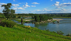 Bow River Valley (LostMyHeadache: Absolutely Free *) Tags: park blue trees houses homes sky green nature water field grass leaves clouds canon river island spring rocks day path branches horizon hill foliage ridge shore valley vista bushes hilltop bowriver davidsmith fishcreekpark calg