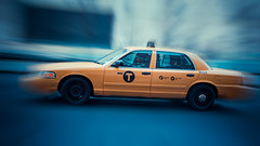 Cab Movement (Darren LoPrinzi) Tags: street city nyc newyorkcity blue urban ny newyork motion blur streets car yellow canon movement zoom manhattan cab taxi wheels fast streetscene tires diagonal uptown transportation vehicle pan panning quick lincolncenter canoneos7d canon7d vision:sunset=0572 vision:clouds=0812 vision:outdoor=0743 vision:sky=0903