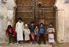 Portugal/Morocco (10) (The Spirit of the World) Tags: children gate door rabat old moroccanchildren posing norhtafrica morocco analogphotography film print scannedprint candid streetscene fence metaldoor irondoor heavy 1986