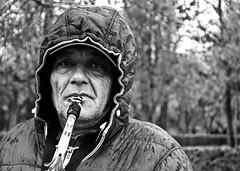 On The Notes Of Life (GianlucaChincoli) Tags: man homeless saxophone music portrait black white contrast rain hood hoodie canon madrid spain sad eyes eyesight