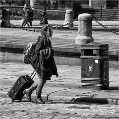 Long haired traveller from Liverpool (John Riper) Tags: johnriper street photography straatfotografie square bw black white zwartwit mono monochrome candid john riper canon 6d 24105 l liverpool england uk traveller dustbin trolley girl long haired backpack walking chain fence walker people pavement jacket coat litter box