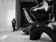 Under the watchful eye of Moonbird (CVerwaal) Tags: nyc sculpture newyork man streetphotography joanmiro texting moonbird solowbuilding microfourthirds leicadgsummilux25f14 panasonicgx7