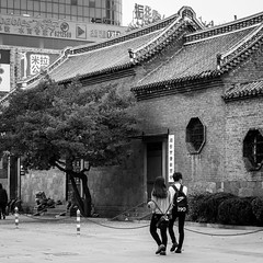 Synchronized (Go-tea ) Tags: canon eos 100d bw bnw black white blackwhite blackandwhithe outside outdoor asia asian china chinese street urban city yantai people man woman boy girl young old palace love couple lovers romantic hands back backside backpack walk walking movement history harmony together alone empty feelings tree roof wall letters nike t90 stairs windows doors chain locked closed