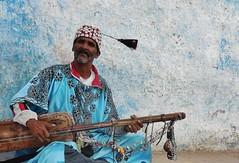 Moroccan musician (SM Tham) Tags: africa morocco rabat kasbahoudayas street musician busker man portrait stringinstrument music traditionaldress skullcap cowries shells wall outdoors