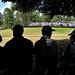 Golf fans enjoy the shade of large trees along the 8th green at Pinehurst No. 2.