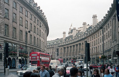 Buildings, Regent Street — London, England (Pythaglio) Tags: street windows roof england people building london cars film buses stone buildings britain united great crowd columns arc structures kingdom flags structure historic sidewalk negative commercial scanned pedestrians british 1989 storefronts curved 1928 chimneys neoclassical ionic capitals 1923 planned curvature dormers mansard 816 sills volutes quoins