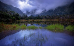 Monsoon dreams (Sapna Reddy Photography) Tags: newzealand petespond water blues blue sky rain clouds cloud pond foliage mountains mountain nature landscape