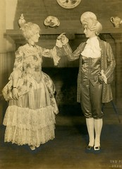 A Couple of Colonial Revivalists (Alan Mays) Tags: ephemera photos photographs portraits foundphotos men women dancers dancing costumes hats clothes clothing dresses ruffles frills coats waistcoats breeches stockings shoes buckles wigs colonial colonialrevival interiors fireplaces bricks handsonhips antique old vintage vptp