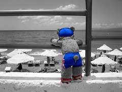 BEAR faced cheek [Explored] (pefkosmad [850k+ views, thanks!]) Tags: blue red sea summer vacation sky bw holiday ted colour beach strand vacances blackwhite sand looking tail bottom hellas bum greece voyeur teddybear budgie flipflops trunks greekislands pe