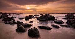 Wistful (RainingEveryday) Tags: ocean light sunset sea sky cloud sun blur beach water clouds landscape photography landscapes photo sand singapore rocks long exposure waves picture wave boulders punggol cloudscape