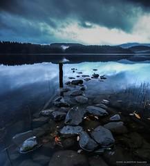 Loch Ard (john&mairi) Tags: loch ard trossachs scotland moody cloudy misty atmospheric water reflection forest post jetty derelict stones rocks clouds