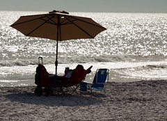 Made in the Shade (grandalloliver) Tags: ocean sunset sea summer vacation people beach water beauty umbrella photoshop canon gulf florida zoom telephoto tiff topaz photoshopelements floridastatepark hss canonef70200mmf4l emeraldcoast canonllens garyoliver southwaltoncounty hwy30a rebelxsi canonxsi topazadjust grandalloliver grandalloliverphoto beachesofsouthwaltoncounty topsailhillstateparkflorida