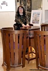 Glasgow Mackintosh City - 7 (Mistress Maggie dot com) Tags: shiny mac mackintosh mature lady woman sitting furniture mackcentre charlesrenniemackintosh glasses pvc coat raincoat plastic black female mistressmaggie chair
