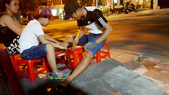 Card sharps (Roving I) Tags: fathers sons playing cards cardgames plasticfurniture streetcafes evening street cafes hats boys fun danang vietnam nightlife