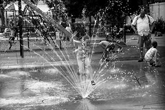 Springing (Swans Fotografies) Tags: nyc summer blackandwhite bw playing newyork game water fountain blackwhite spring eau child play noiretblanc heat jugar littlegirl été enfant fontaine joue noia aigua jeu calor estiu joc chaleur waterjets sortidor brollador petitefille jouant jetsdeau dollsdaigua