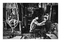 Scenes of a memory. (Shutterfreak ☮) Tags: life street people man metal shop hardware nikon child feeding sandals candid homeless pipes oldman daily bamboo clothes textures shanty dhaka moment bangladesh cylinders sacks streetside d5000 inkiadhasin pod198