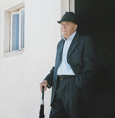 (Nasos Zovoilis) Tags: door camera old family summer portrait people white plant man flower male men green love home window nature senior face look hat shirt forest garden bench season relax outside happy person one back clothing still healthy couple village sad adult outdoor grandfather working handsome lifestyle happiness athens read hasselblad greece relationship mature elderly age single greenery rest casual leisure years aged wisdom middle relaxation retired unhappy economy crisis carefree retirement active caucasian pensioner vision:text=0609 vision:outdoor=0682