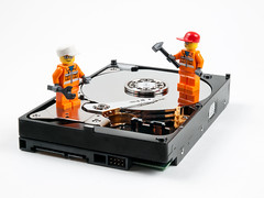 hdd redwoodgardens character computer computerparts cylinder disc disk diskdrive harddisk harddrive indoors inside interior lego macro minifigure mirror needle object opened orange plate playful storage tech technology tools toy toys whitebackground workmen