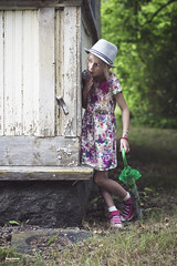 """Hope they don't see me"" (salas-3) Tags: girl summer building house warm beautiful hat umbrella dress playing child story nikon photography"