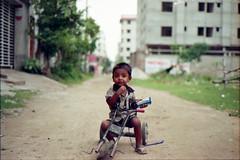 Happy Prince of the Street (Sheikh Shahriar Ahmed) Tags: street film analog kid child tricycle streetlife fujifilm dhaka bangladesh banasree nikonf6 childportrait kidportrait af50mmf18d fujicolorc200 dhakadivision epsonv330 sheikhshahriarahmed