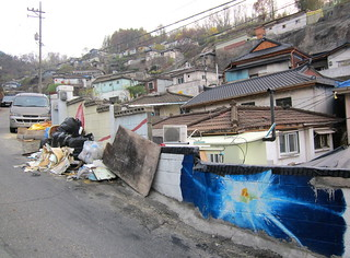 Seoul Korea hillside ant village slum shanty area with colorful murals dukeing it out with cluttered junk -